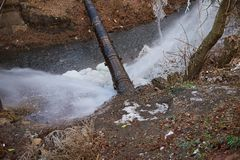 Water flow from the pipe. Water pressure from a large pipe over the river, in winter stock image