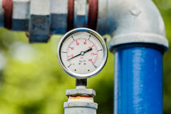 Water pressure meter. Installed on a blue pipe stock photography