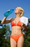 Water. Pretty blond in bikini drinking water Royalty Free Stock Photos