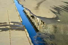 Water in a puddle on the roadside of an urban asphalt road with. A reflection of the house stock photography