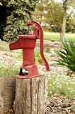 Water Pump. An antique, red water pump mounted on a log stock photos