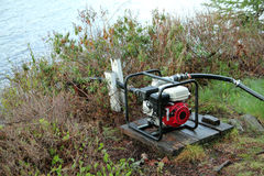 Water pump. Portable water pump near a lake in a forest royalty free stock images