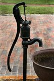 Water pump. Black,iron,antique water pump next to iron trough beside red brick sidewalk and green grass stock image