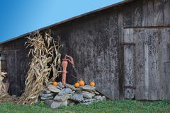 Water pump and barn. This image is of an old hand operated water pump on a working farm. It is decorated for seasonal visitors to the farm Stock Image