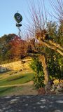 Historical Water pump. French Wind driven historical mechanical water pump located in garden surrounded by stone wall and trees in late autumn sunlight Under Royalty Free Stock Photography