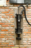Water Pump. Old hand water pump in a brick wall Royalty Free Stock Photos