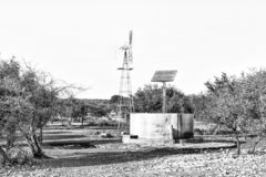 Water-pumping windmill and solar panels for a waterpump. Monochrome royalty free stock photos