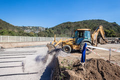 Water Purification Canal Construction. At new Durban Solid waste processing plant mid way in construction. Grader poring stone fill into canal structure layout Royalty Free Stock Image