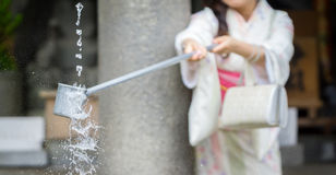 Water purification at entrance of Japanese temple #3. Woman in traditional dressing takes water for purification at the entrance of Japanese temple #3 Royalty Free Stock Photos