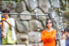 Water purification at entrance of temple. Water for purification at the entrance of Japanese temple with people waiting Royalty Free Stock Photo