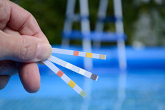 Water quality is tested. Hand with measuring strips to control water quality in swimming pools Stock Photography