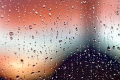 Water rain drops on the window glass on sunset. Shallow depth of field. Cityscape silhouette.  Stock Photos