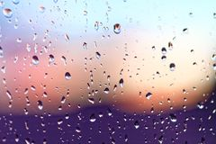 Water rain drops on the window glass on sunset. Shallow depth of field. Cityscape silhouette.  Stock Photography