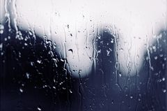 Water rain drops on the window glass on sunset. Shallow depth of field. Cityscape silhouette.  Stock Photo