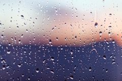 Water rain drops on the window glass on sunset. Shallow depth of field. Cityscape silhouette.  Stock Image