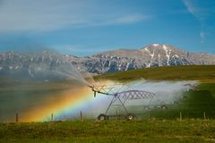 Water rainbow efect around spraying machine, Southern Alberta, Canada. Farming land, wild west stock images