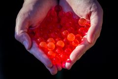 Water red gel balls. Small gel ball in the hand. Polymer gel. Silica gel. Balls of red hydrogel. Crystal liquid ball with reflecti royalty free stock photo