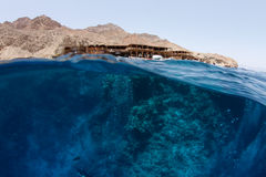 Water with reef and desert mountains. Half half shot of the Blue Hole in Dahab, South Sinai, Egypt royalty free stock photography