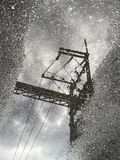Water reflection of cable and electric pole. On the cement road Stock Images
