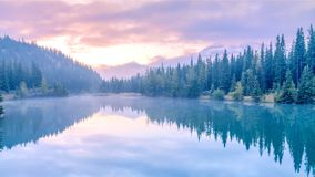 Water reflection of Cascade lake with morning mist and sunrise , Banff National park. Alberta, Canada stock images