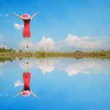 Water Reflection Happy Woman Jumping with blue sky Royalty Free Stock Image