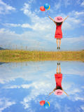 Water Reflection Happy Woman Jumping with blue sky Stock Photography