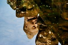 Water reflection of statue in Historic building in Angkor wat Thom Cambodia. With devatas carvings stone faces serenity milk ocean Royalty Free Stock Images
