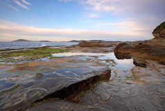 Water reflections at the rocky shore line. Beautiful morning reflections at sunrise with a rocky shoreline stock images