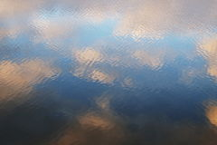 Water reflections of the sky on the lake. Ripples and mirror effect royalty free stock photo