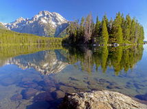 Water reflections of snow capped mountains and green trees. Stock Photo