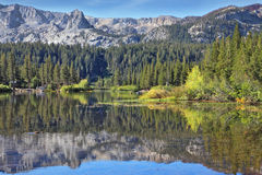 In the water reflects the majestic mountains Stock Photo