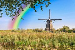 Rainbow over the Windmill at Kinderdijk. Water Reflexion over the Windmill and the landlord house at Kinderdijk listed in the UNESCO heritage list Stock Image