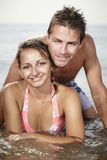 Water relaxing couple. Young couple relaxing at beach in Italian resort Caorle bathing in sea water and summer sun royalty free stock photography