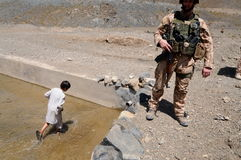 Water reservoir in Afghanistan. An Afghan boy walking in the water reservoir built by Czech Republic´s Provincial Reconstruction Team (PRT) in Chinarey village Stock Photos