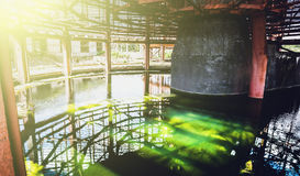 Water reservoir with green water of abandoned cooling tower in sun light Royalty Free Stock Image