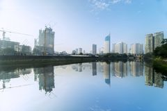 Water reservoir with skyscrapers under clear sky Royalty Free Stock Photos