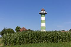 Water reservoir tower under blue sky and green field Royalty Free Stock Photo
