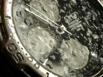 Water resistant watch. Water resistant high tech watch splashed with water drops stock photos