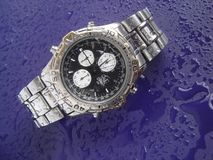 Water resistant watch. Water resistant high tech watch splashed with water drops royalty free stock photography