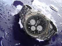 Water resistant watch. Water resistant high tech watch splashed with water drops stock image