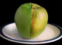 Water on ripe apple. Drops of water on ripe apple split into two different shades of green; black background Stock Photo
