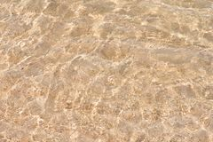 Water rippled and sunny reflections on the surface of gold sand in the sea.  royalty free stock photography