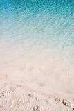 Water ripples sandy beach. Calm aqua blue water ripples making reflections on a sandy beach Stock Image