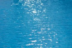 Water ripples texture in swimming pool with sunny glare. Blue water ripples texture in swimming pool with sun flare Royalty Free Stock Images