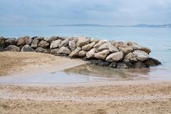 Water and rocks winter beach. Water and rocks on sandy tranquil Mediterranean winter beach in Mallorca, Balearic islands, Spain in February Stock Image