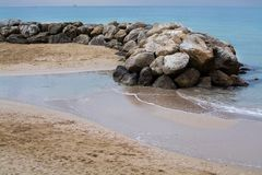 Water and rocks winter beach. Water and rocks on sandy tranquil Mediterranean winter beach in Mallorca, Balearic islands, Spain in February Stock Images