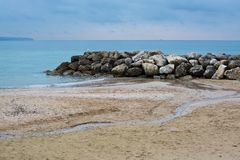 Water and rocks winter beach. Water, rocks, seagull and meandering water on sandy tranquil Mediterranean winter beach in Mallorca, Balearic islands, Spain in Royalty Free Stock Photo