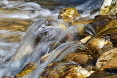 Water rolling over yellow stones in a wild river. In the mountains in Italy Stock Photo