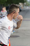 Water. Runner drinking and running at the 2013 Peoria IL Marathon Royalty Free Stock Photo