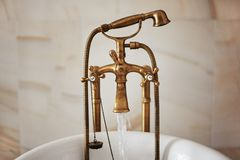 Water running down from antique bronze faucet tap into the bathtube. Indoors, stylish interior, copy space stock photo